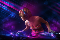 Young DJ playing on turntables with color light effects Stock Image