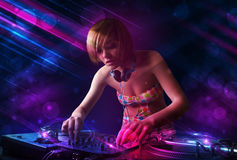 Young DJ playing on turntables with color light effects. Beautiful young Dj playing on turntables with color effects Stock Photo