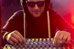 Young dj beside turntable. Young dj wearing sunglasses, standing beside turntable Royalty Free Stock Photos