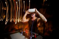 Young DJ in virtual reality glasses plays the track in club. Young DJ in virtual reality glasses, dressed in black shirt and with tattoo plays the track in club Royalty Free Stock Images