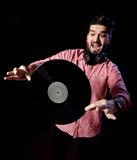 Young DJ in white costume holding vinyl record in Stock Images