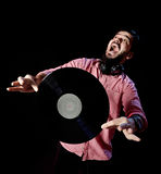 Young DJ in white costume holding vinyl record in. Isolated black bakcground. young man looking up, surprise Stock Image