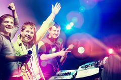 Young DJs playing records at a party in a nightclub. Looking at camera and smiling. Royalty Free Stock Photo