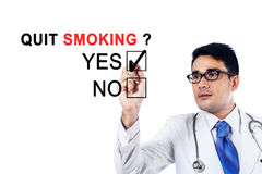 Young doctor agreeing about quit smoking. Image of young male doctor using a pen while agreeing about quit smoking on the whiteboard Royalty Free Stock Photos