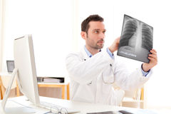 Young doctor analysing a radiography. View of a young doctor analysing a radiography stock photo