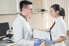 Young doctor and assistant standing and holding folder tablet Stock Photos