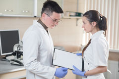 Young doctor and assistant standing and holding folder tablet Royalty Free Stock Photos