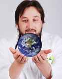 Young doctor with beard is holding earth in hands Royalty Free Stock Photos