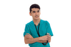 A young doctor in the blue dress with stethoscope folded hands together and smiling. Isolated on white background Royalty Free Stock Photo