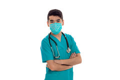 A young doctor in a blue dress with a stethoscope and a mask on the face. Isolated on white background Royalty Free Stock Photo