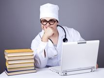 Young doctor with books and computer. Royalty Free Stock Image