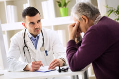 Young doctor carefully listening patient about his pains Royalty Free Stock Photography