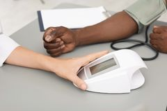 Young doctor checking African-American patient`s. Blood pressure in hospital stock photo