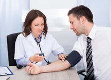 Young doctor checking blood pressure Stock Image