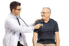 Young doctor checking up a mature male patient with a stethoscope. Isolated on white background stock photography
