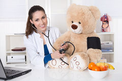 Young doctor for children with a teddy bear. Royalty Free Stock Photography