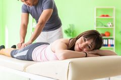The young doctor chiropractor massaging patient. Young doctor chiropractor massaging patient royalty free stock images