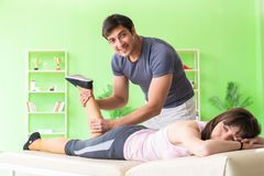 The young doctor chiropractor massaging patient. Young doctor chiropractor massaging patient stock photos