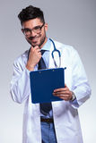 Young doctor with clipboard touches his chin and smiles Royalty Free Stock Images
