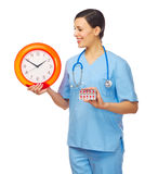 Young doctor with clock and pills Royalty Free Stock Images