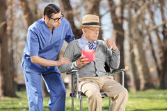 Young doctor comforting a sad senior in a park Royalty Free Stock Photo