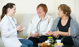 Young doctor consulting senior petients in domestic interior Stock Image