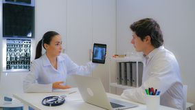 Physician talking with assistant in white office. stock images