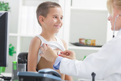 Young doctor examines the boy's back with stethoscope Stock Images