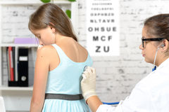 A young doctor examines a little girl Stock Photography