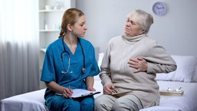 Young doctor examining elderly lady complaining on heart pain, writing diagnosis royalty free stock images
