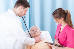 Young doctor examining elderly lady Royalty Free Stock Photography