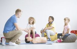 Doctor explaining first aid steps. Young doctor explaining first aid steps to a group of kids using a medical dummy royalty free stock image