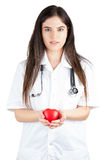 Young Doctor  Gently Holds A Heart. Young Doctor With Stethoscope Gently Holds A Heart Royalty Free Stock Photography