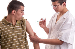 Young doctor give an injection to a pacient who is very afraid o Stock Photo