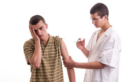 Young doctor give an injection to a pacient who is very afraid o Royalty Free Stock Photos
