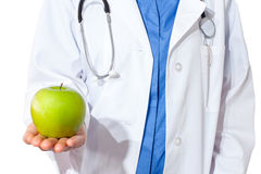 Young  doctor giving an green apple. Royalty Free Stock Photos