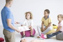 Doctor giving kids pamphlets stock image
