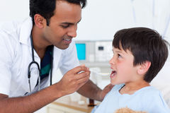 Young doctor giving medicine to a little boy Stock Image