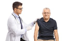 Young doctor giving a shot to a mature man royalty free stock photos