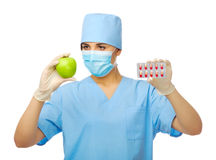 Young doctor with green apple and pills Royalty Free Stock Photo