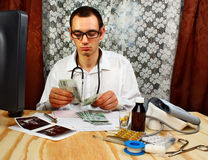 The young doctor has earned money. In doctor's office Royalty Free Stock Photography