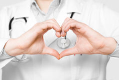 Young doctor with heart shaped fingers. Stock Photo