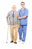Young doctor helping an elderly gentleman with crutch Stock Photography