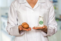 Young doctor holding eggs and bottle of pills with vitamins and Royalty Free Stock Photos