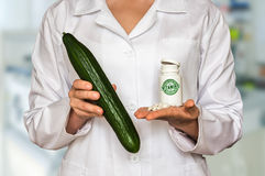 Young doctor holding fresh cucumber and bottle of pills with vit Stock Photography