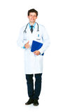 Young doctor holding a notepad and finger up on white background Royalty Free Stock Images