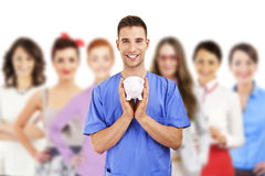Young doctor holding piggy bank. Over white background and team of people Stock Image