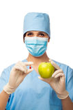 Young doctor holding pill and apple Royalty Free Stock Photo