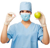 Young doctor holding pill and apple Stock Images