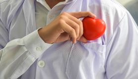 Young doctor holding a red heart near the pocket healthcare and medical concept.  royalty free stock photo